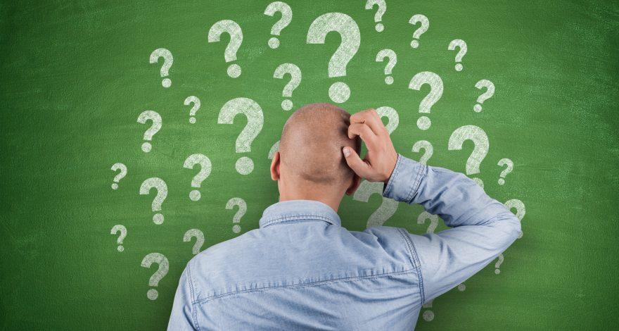 Question Marks on black Blackboard with businessman